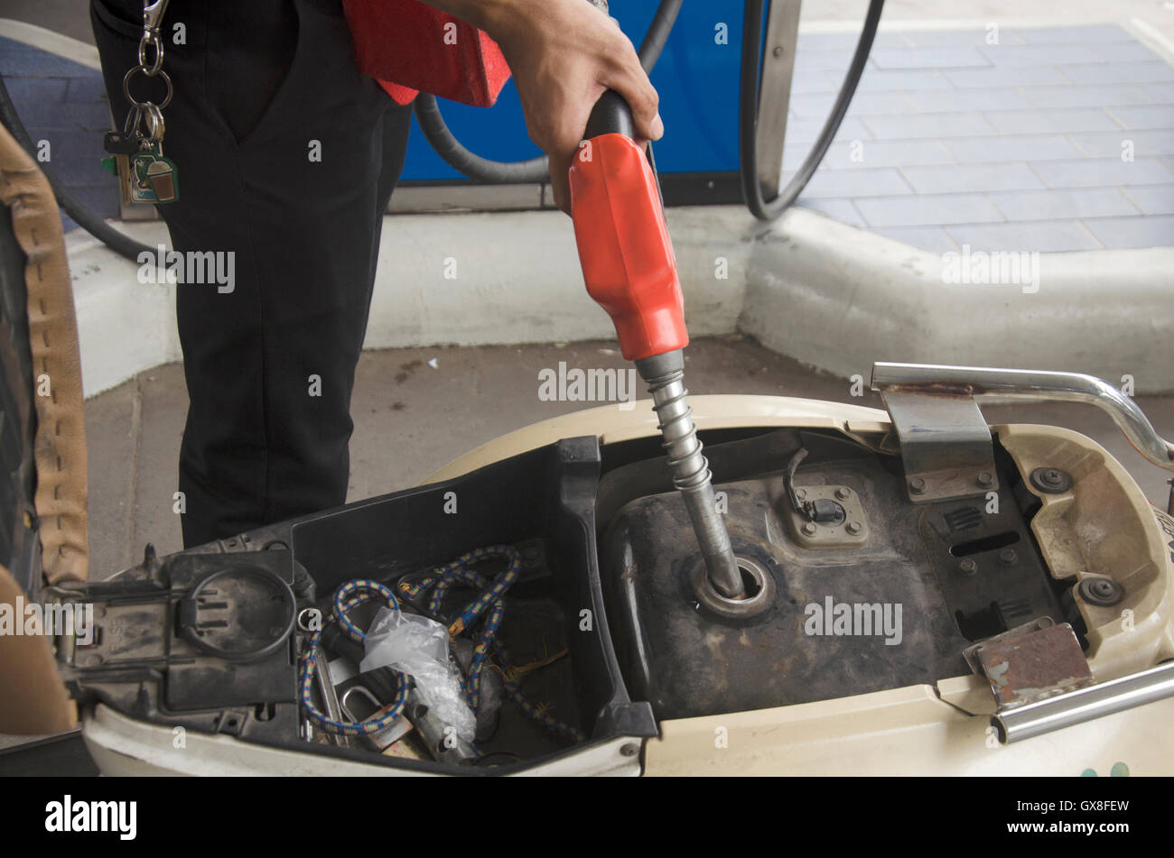 2110df5f9107f2 Thai people use gas pump nozzle filling gasoline fuel to tank of motorcycle  in oil station