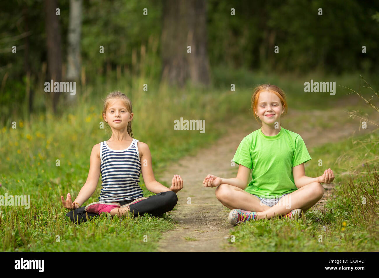 Two little cute yoga girls sitting in Lotus position outdoors. - Stock Image