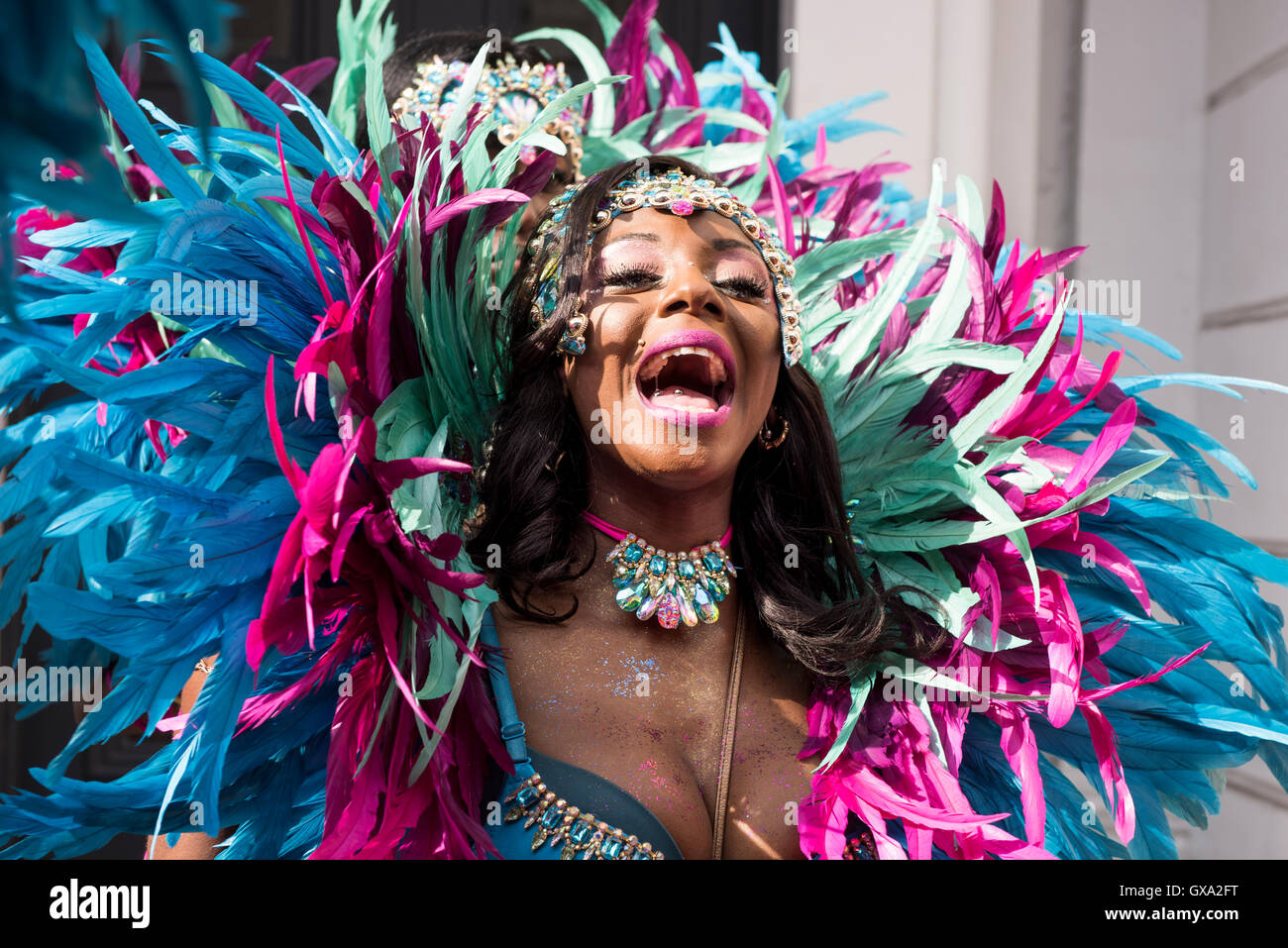 Reveller laughing while chatting to her friends at Notting Hill Carnival - Stock Image