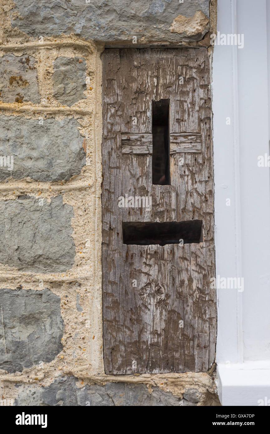 Old original wooden posting box in a wall in Lyme Regis, Dorset UK - Stock Image