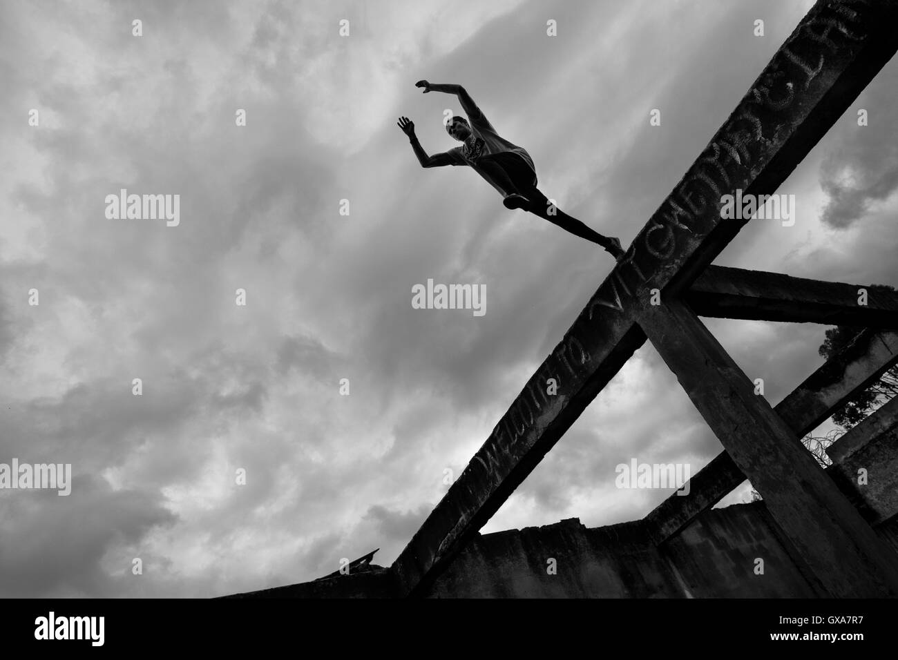 Jose Rodriguez, a freerunner from Plus Parkour team, jumps from the top of the ruined walls in Bogotá, Colombia. - Stock Image