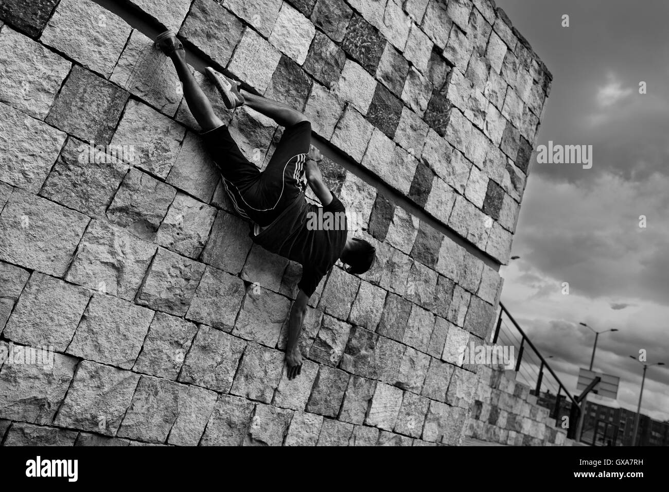 A Colombian parkour athlete shows off his climbing skills during a free running training exercise in Bogotá, - Stock Image