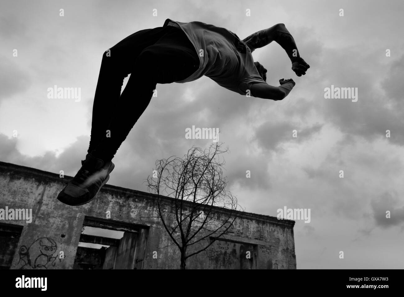Jose Rodriguez, a parkour athlete from Plus Parkour team, does a back flip in Bogotá, Colombia. - Stock Image