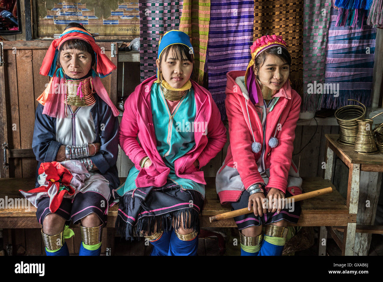 Three women of the Kayan Lahwi tribe wearing traditional metal rings on their necks - Stock Image