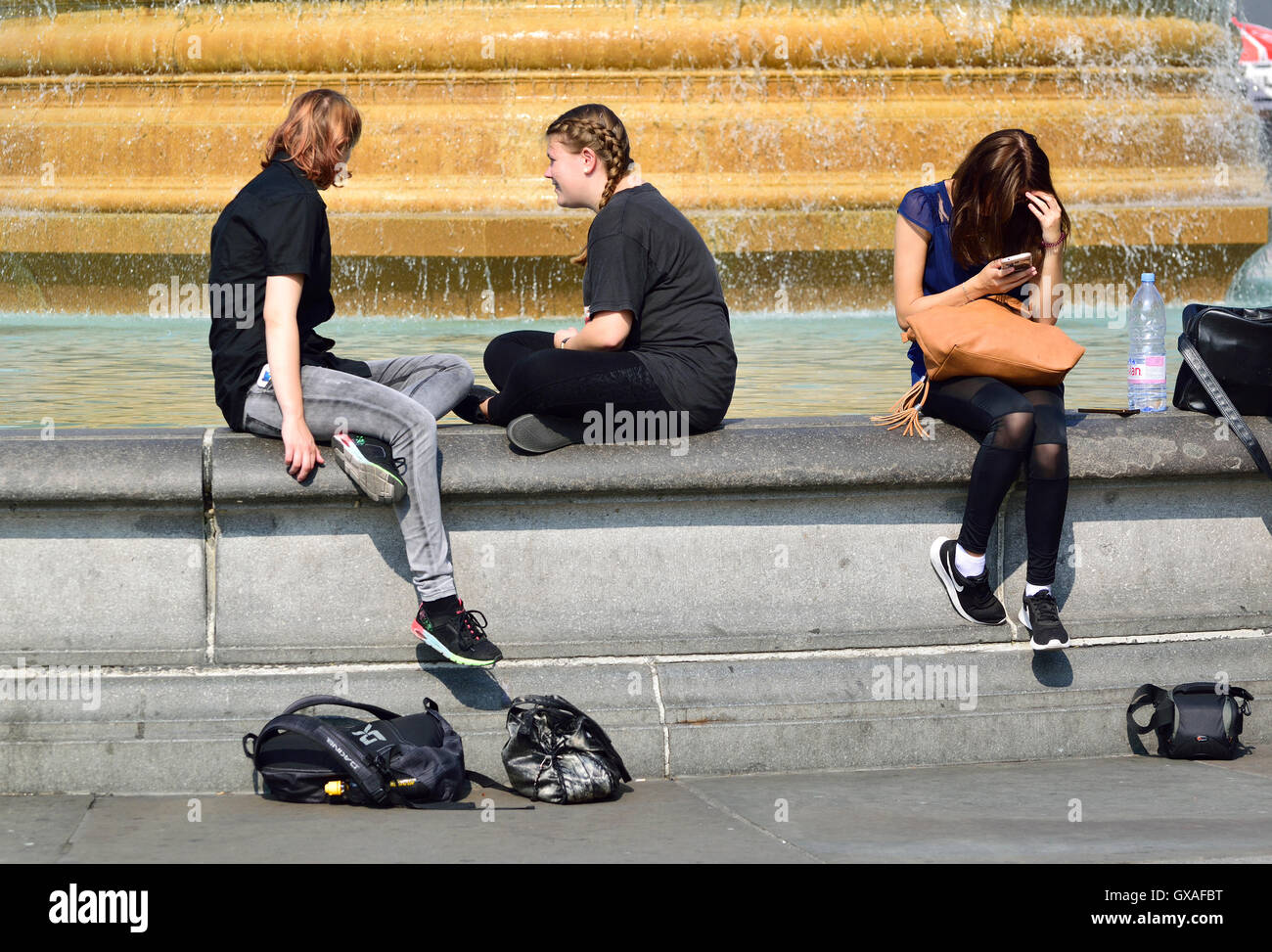 London, England, UK. Trafalgar Square - young people sitting on one of the fountains. Stock Photo