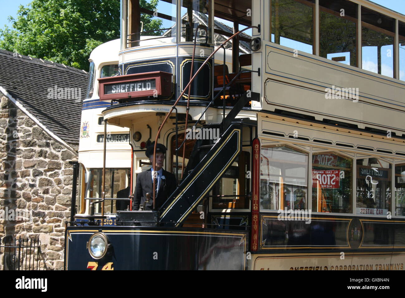 A conductor climbs the stairs of Tram 74 formerly belonging to Sheffield Corporation Tramways, now at Crich Tramway Stock Photo