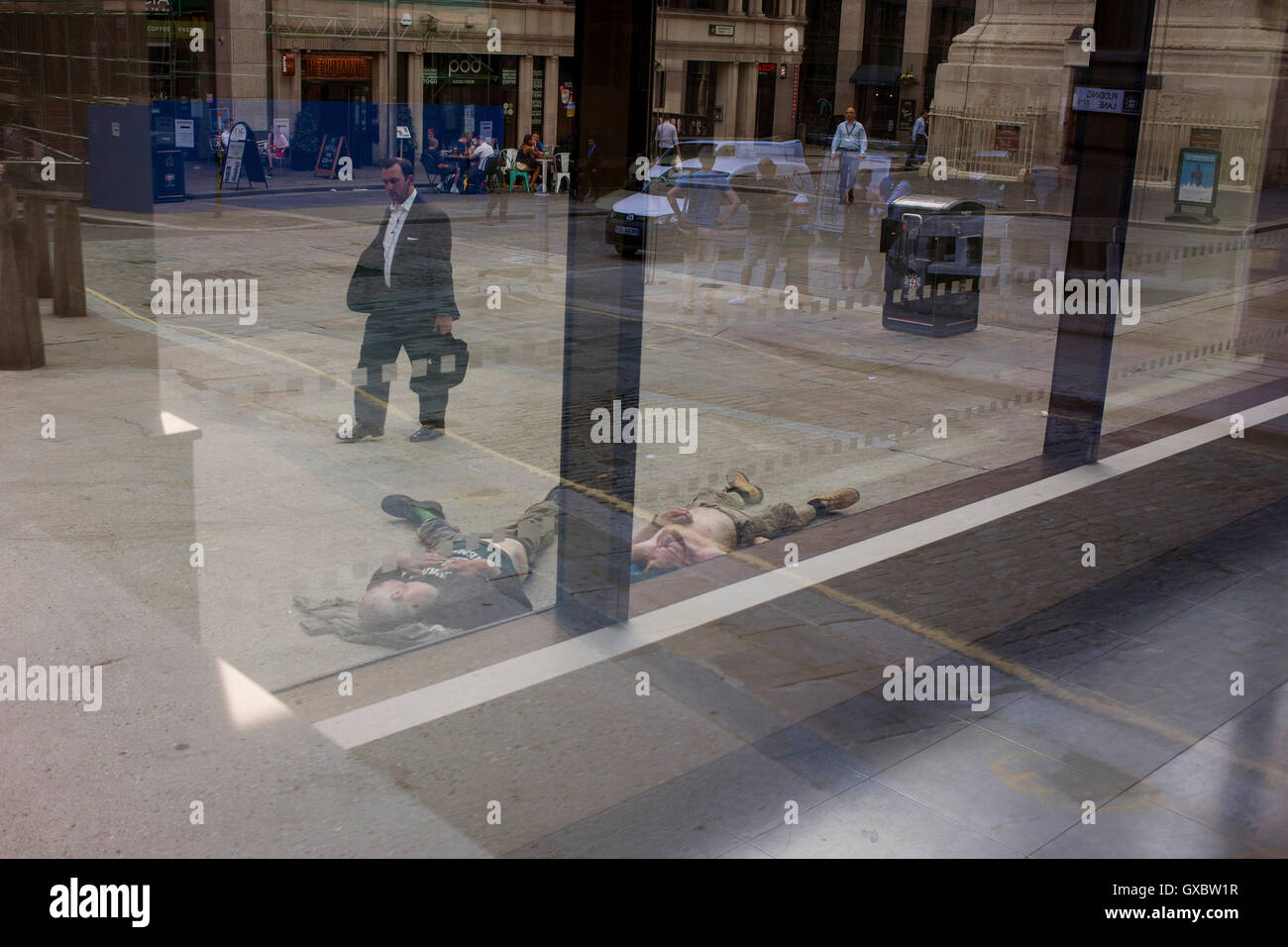 Two men sleep on the ground near Pudding lane, the location of the Great Fire of London (1666), on 13th September Stock Photo
