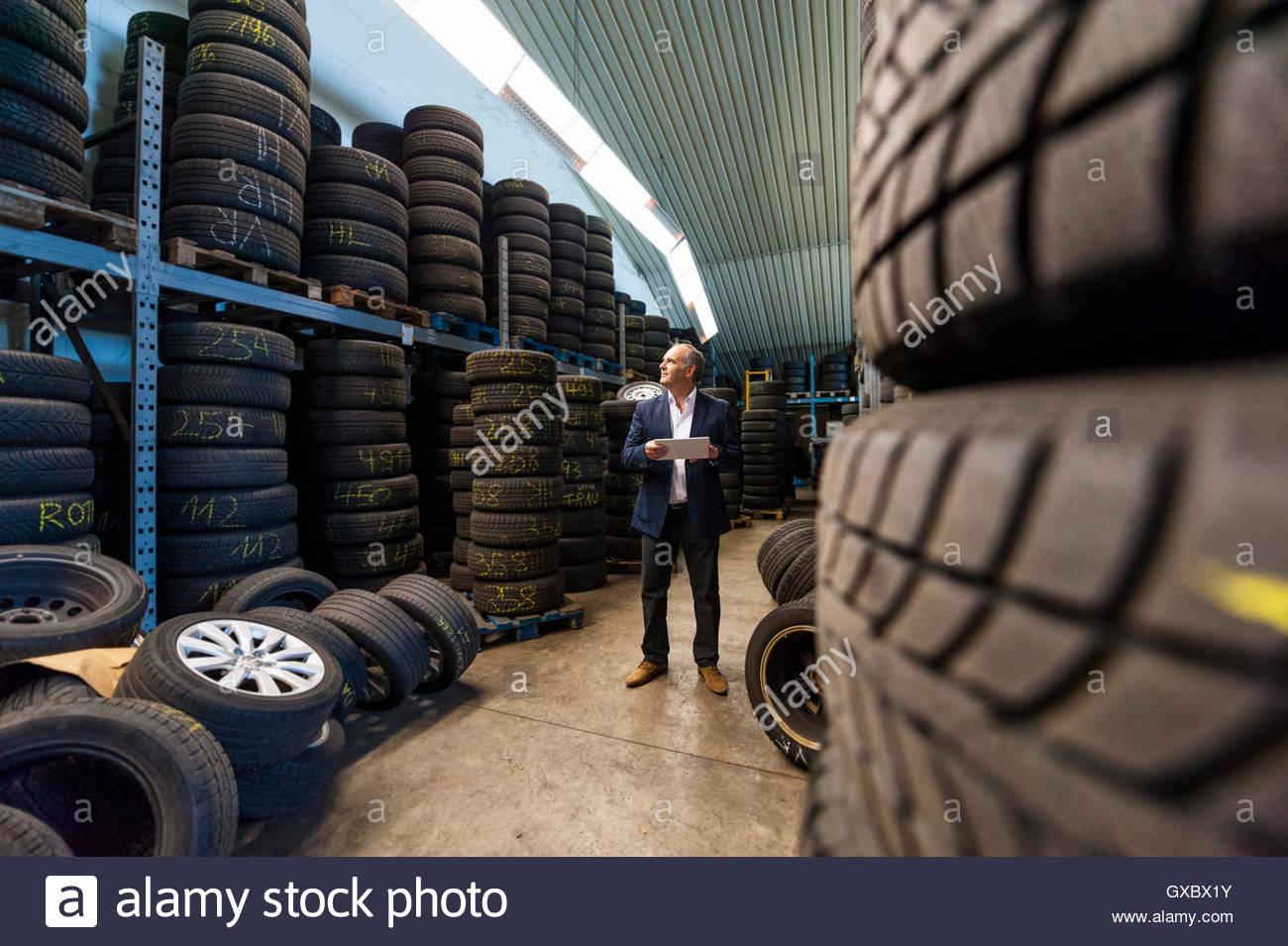 Senior business owner with digital tablet counting stacked tyres in garage - Stock Image