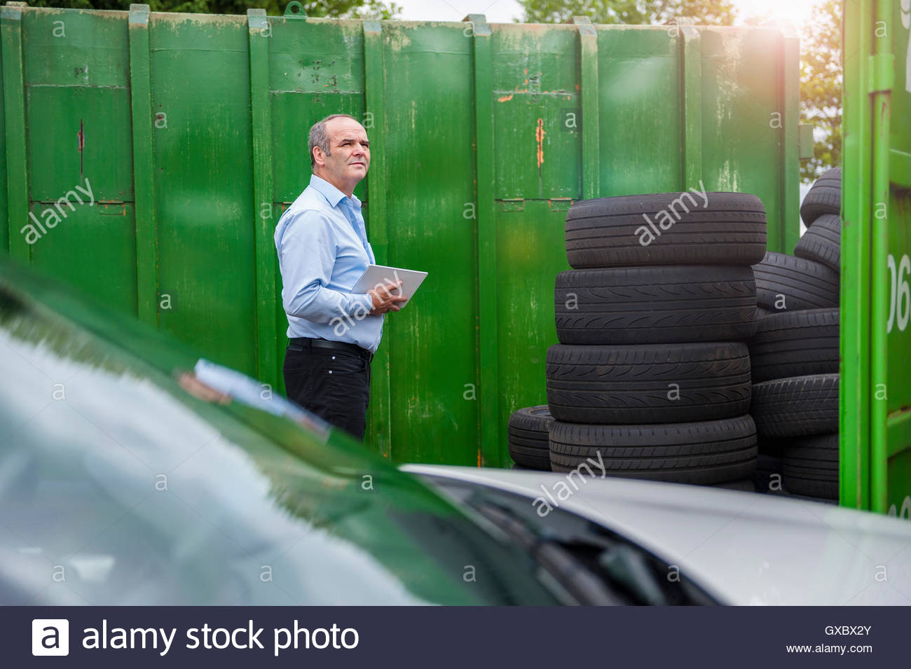 Senior male business owner monitoring stacked tyres in repair garage yard - Stock Image