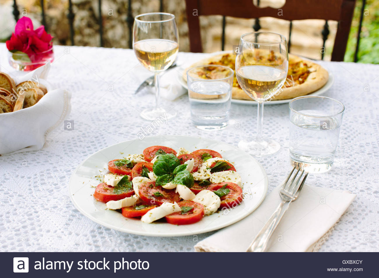Al fresco table with rustic pizza and caprese salad, Cilento, Italy - Stock Image