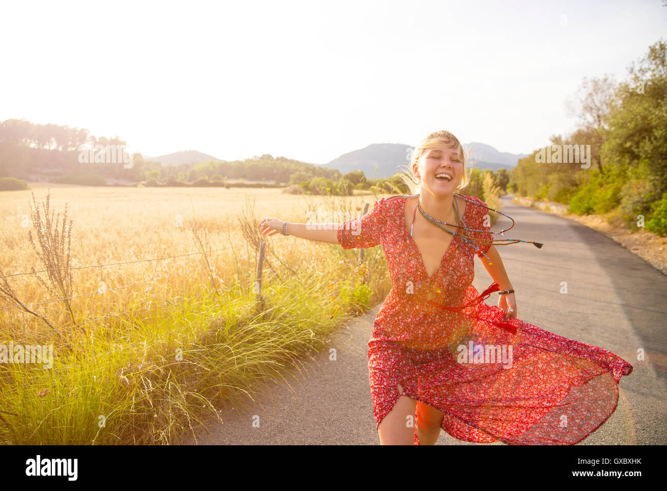 Young woman running and laughing on rural road, Majorca, Spain Stock Photo