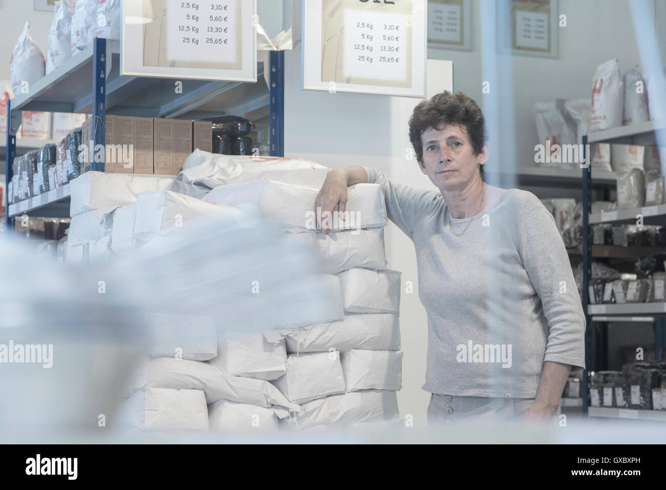 Portrait of female miller and flour sacks in wheat mill stockroom Stock Photo