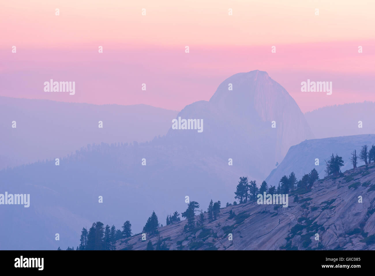 Half Dome at sunset, the mountain partially obscurred by smoke from the 2014 Dog Rock wildfire, Yosemite, California, - Stock Image