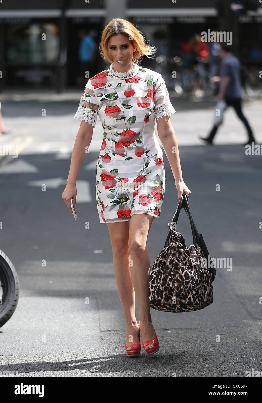 Stacey Solomon wearing a rose patterned minidress and red high heels while out and about in London  Featuring: Stacey - Stock Image