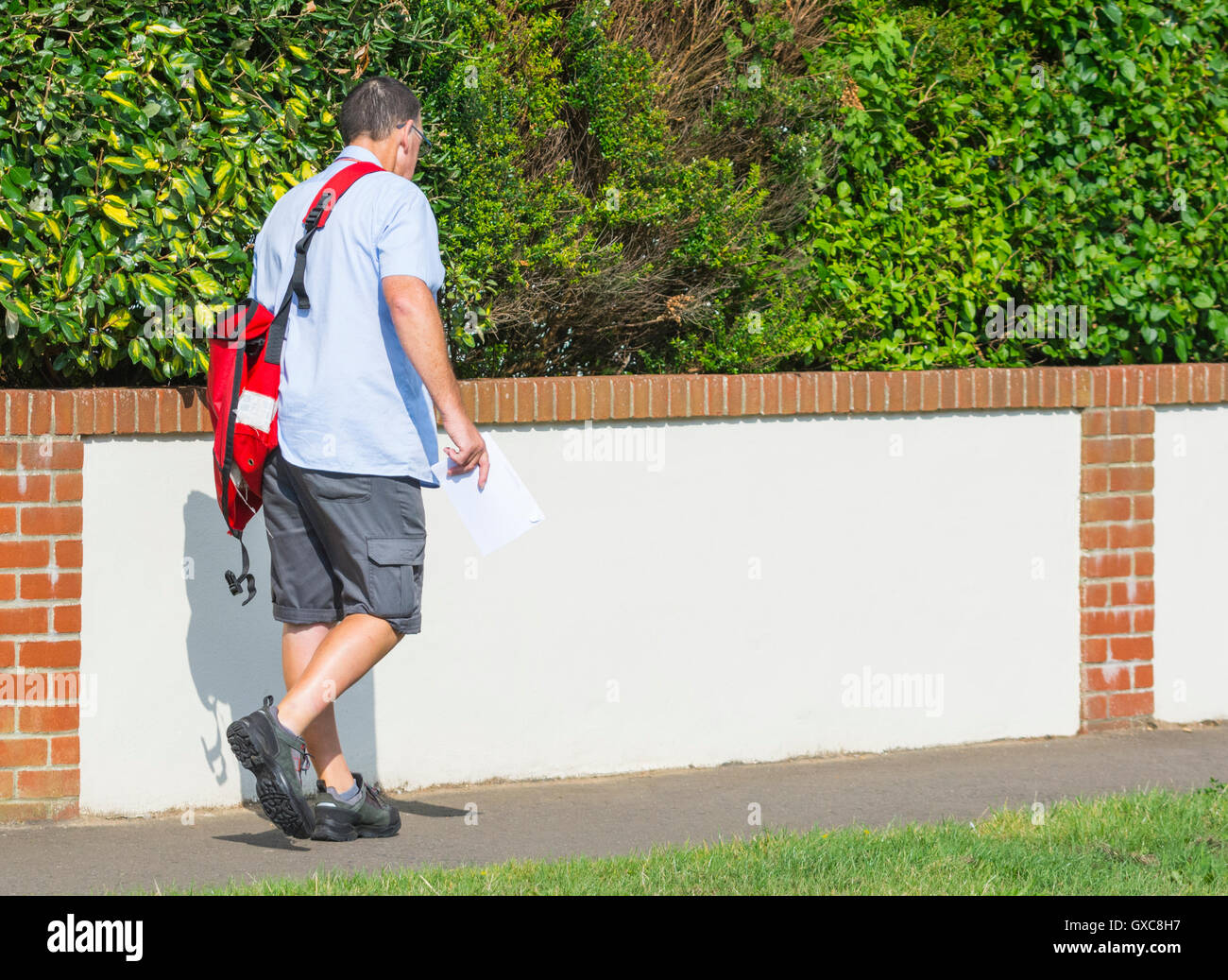 Royal Mail postman on his post delivery round in the UK. - Stock Image