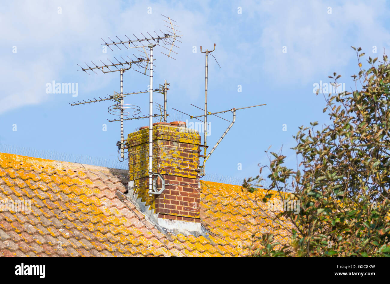 Multiple TV aerials mounted on a chimney on a terrace of houses in the UK. - Stock Image