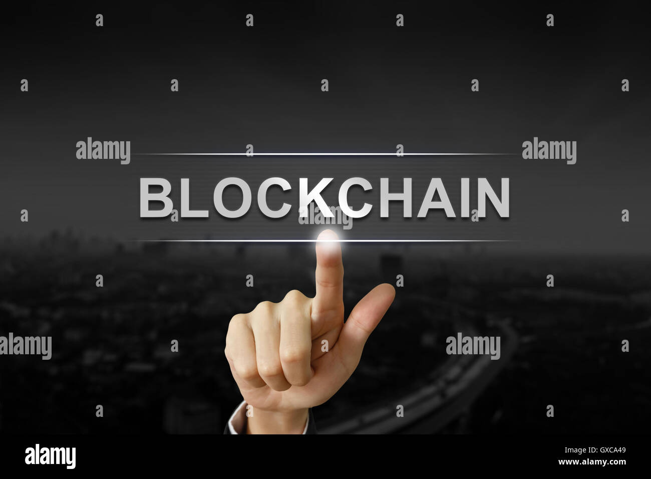 business hand clicking blockchain button on black blurred background - Stock Image