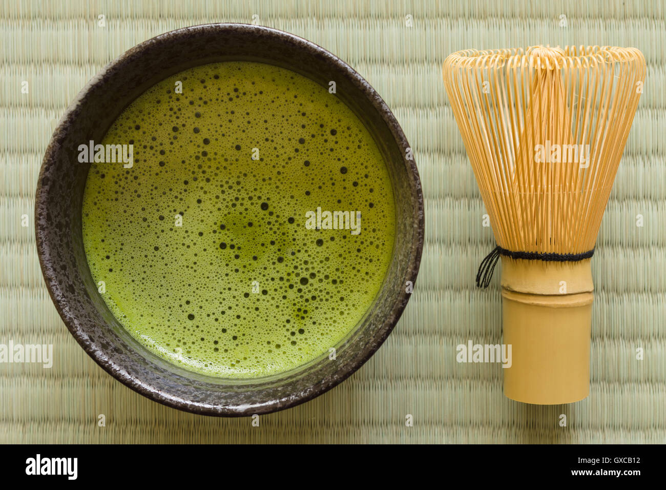 Japanese Matcha green tea in a chawan or traditional ceramic bowl with a chasen or bamboo whisk - Stock Image