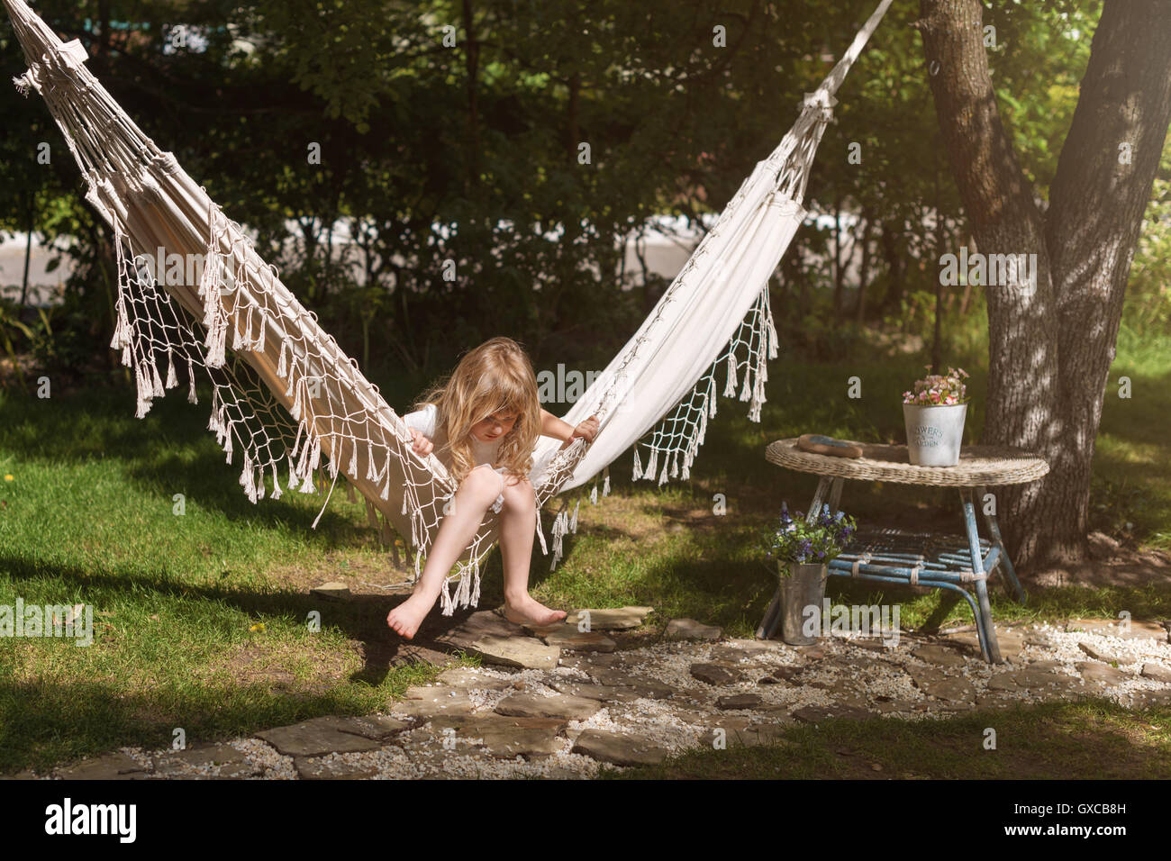 Little girl swinging in a hammock and having fun outdoor. Child ...