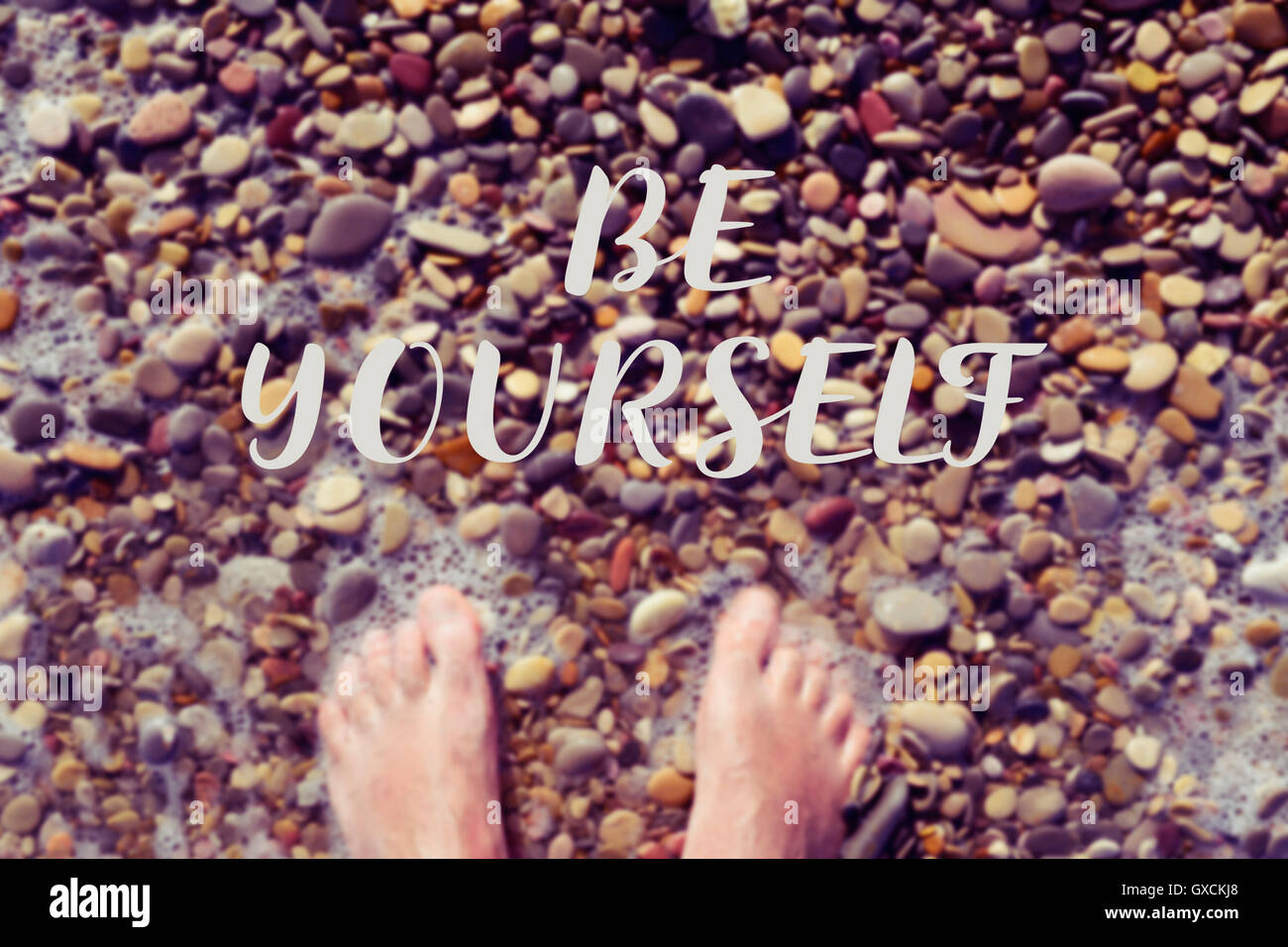 high-angle shot of the bare feet of a young caucasian man in the seashore of a shingle beach, and the text be yourself - Stock Image