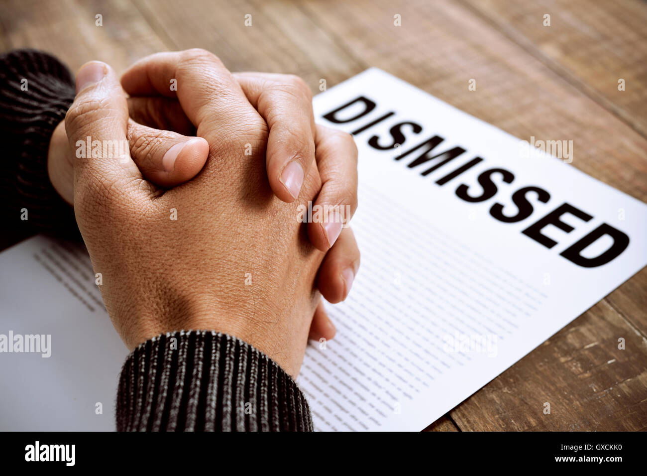 closeup of the clasped hands of a young caucasian man on a document with the text dismissed, placed on a rustic - Stock Image