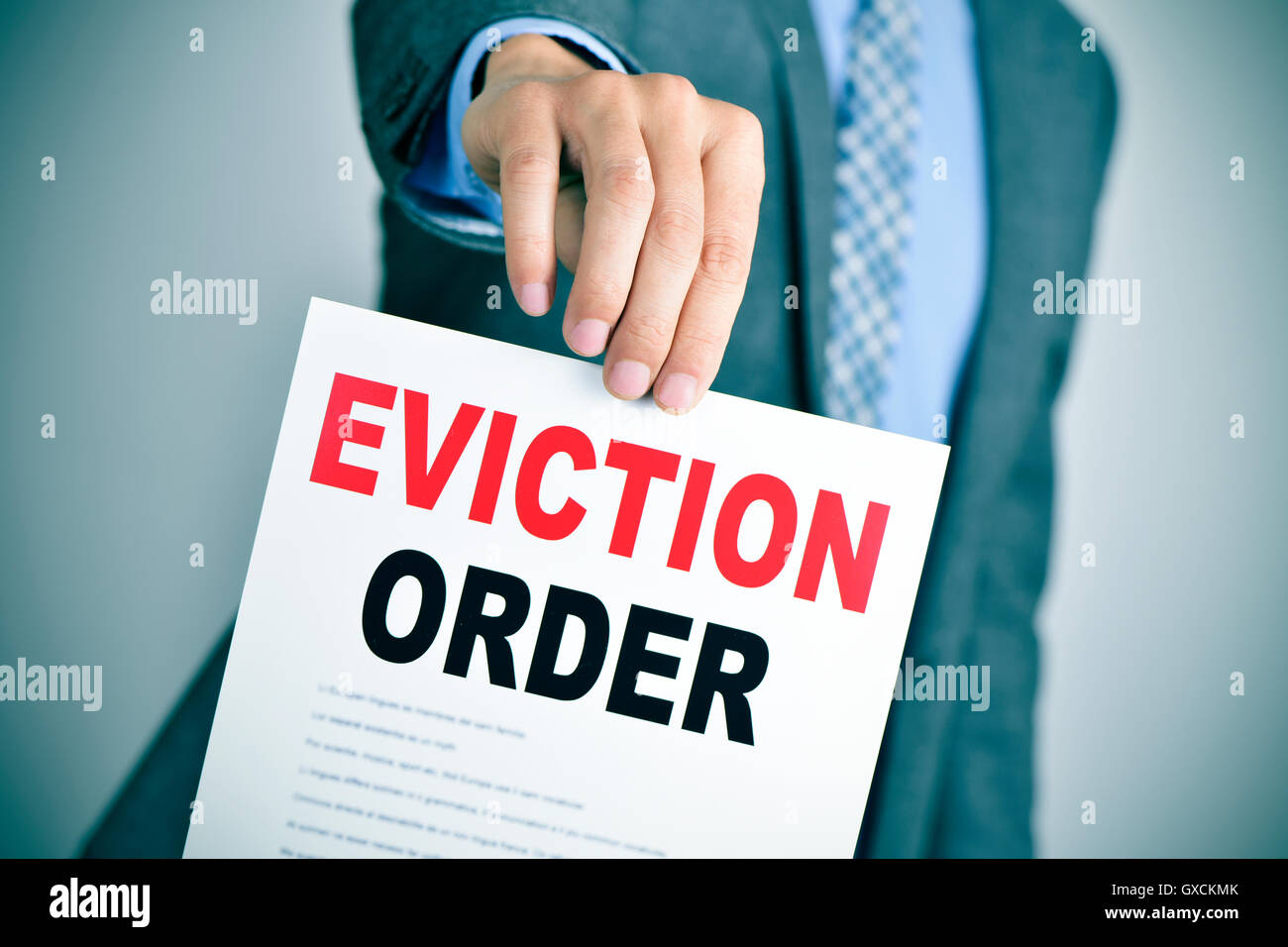 a young caucasian man wearing a gray suit shows a document with the text eviction order - Stock Image