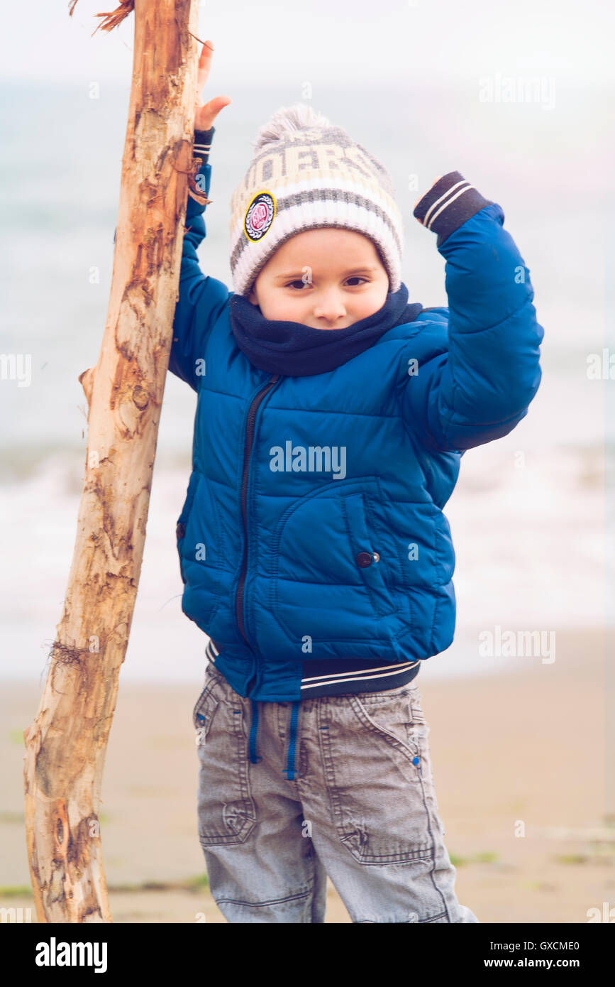 child climbing on a pile of sand in Winter Beach - Stock Image
