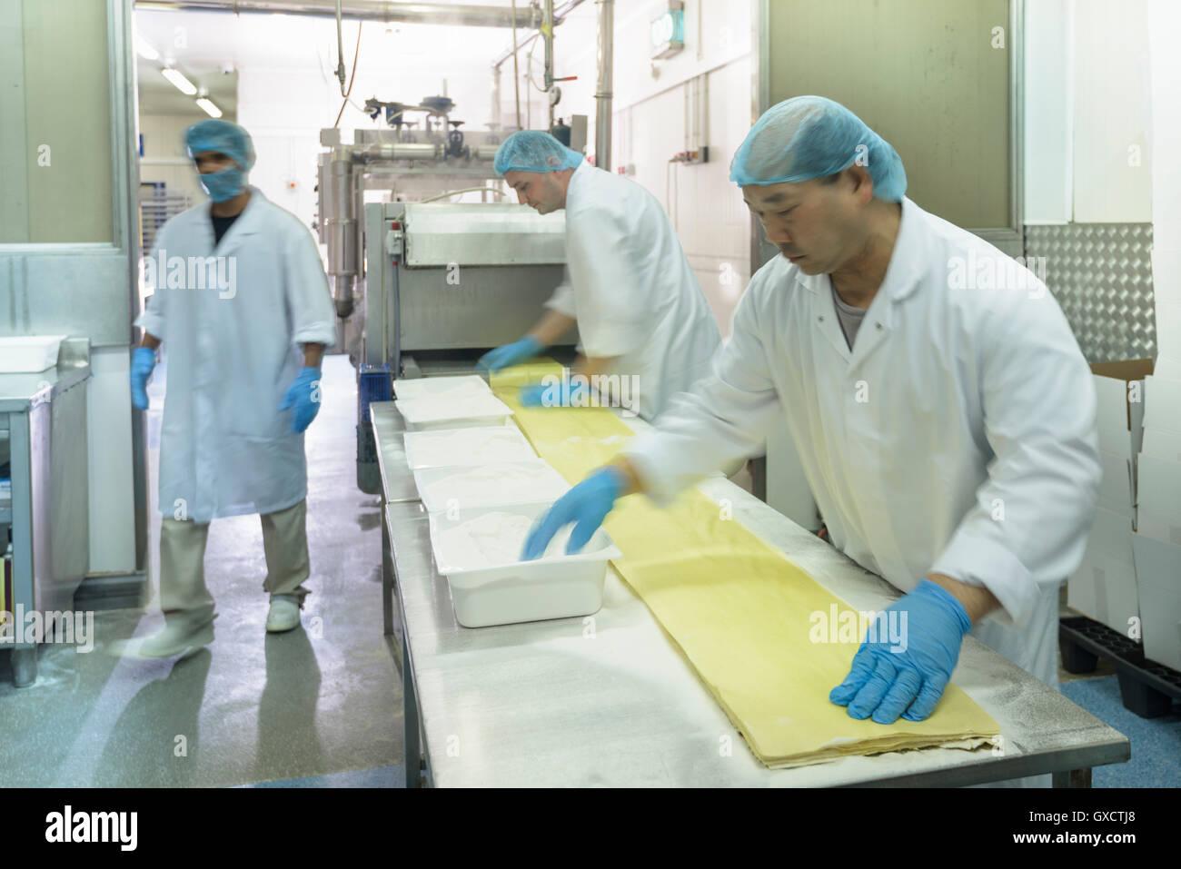Workers making fresh pasta sheet in pasta factory - Stock Image