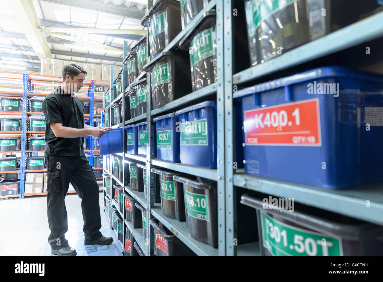 Worker choosing parts in electrical parts factory - Stock Image