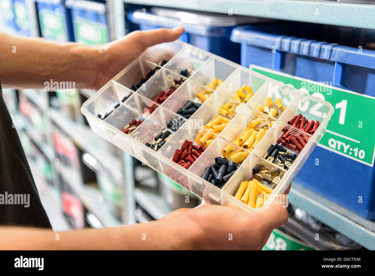 Worker choosing parts in electrical parts factory, close up - Stock Image