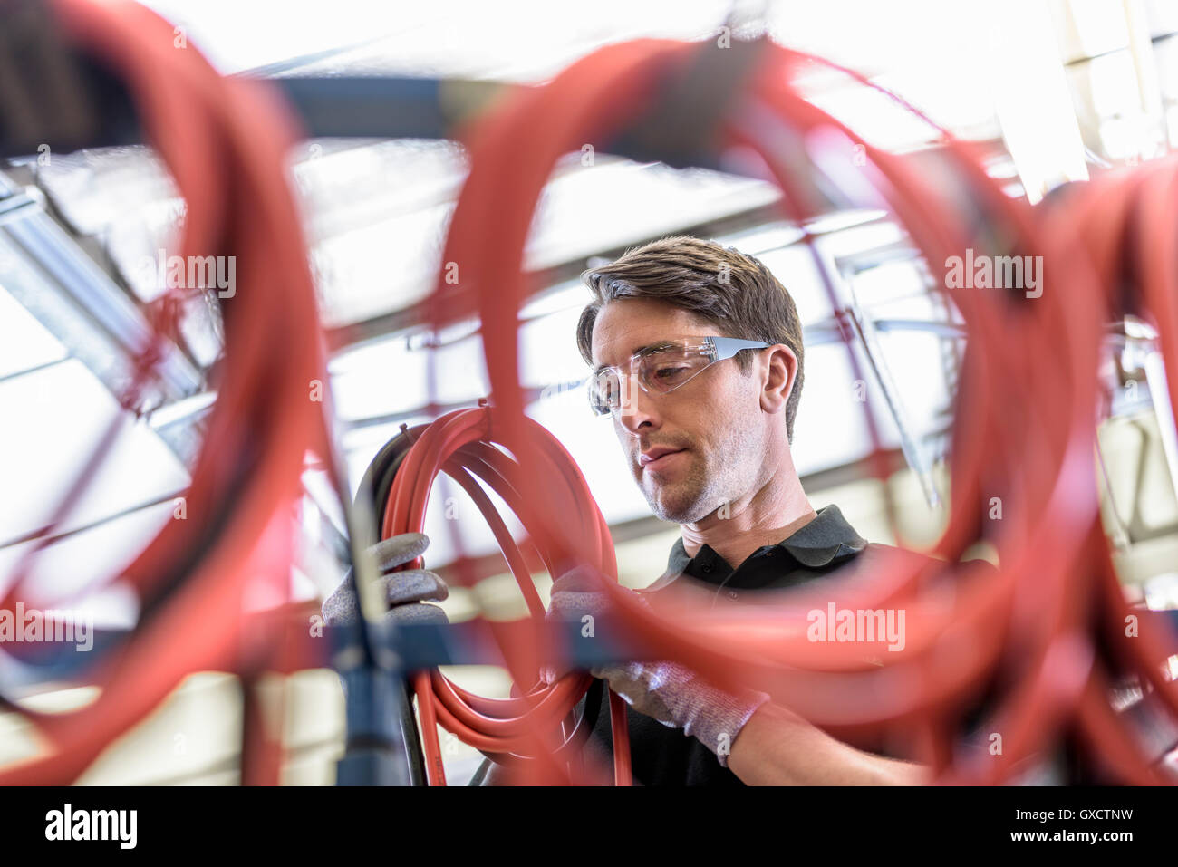 Worker making cable lengths in electrical cable factory - Stock Image