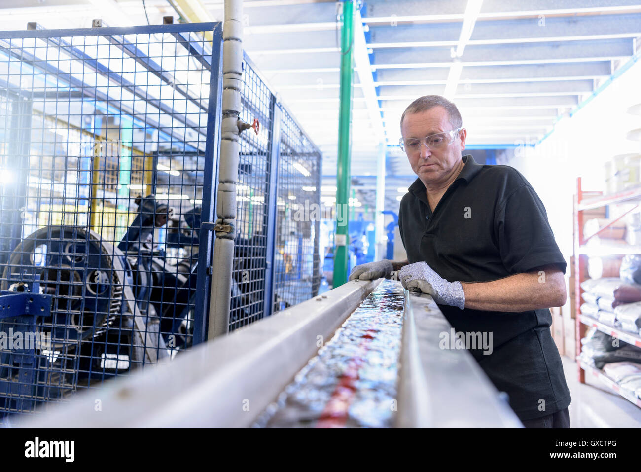 Worker running electrical cable through cooling bath in cable factory - Stock Image