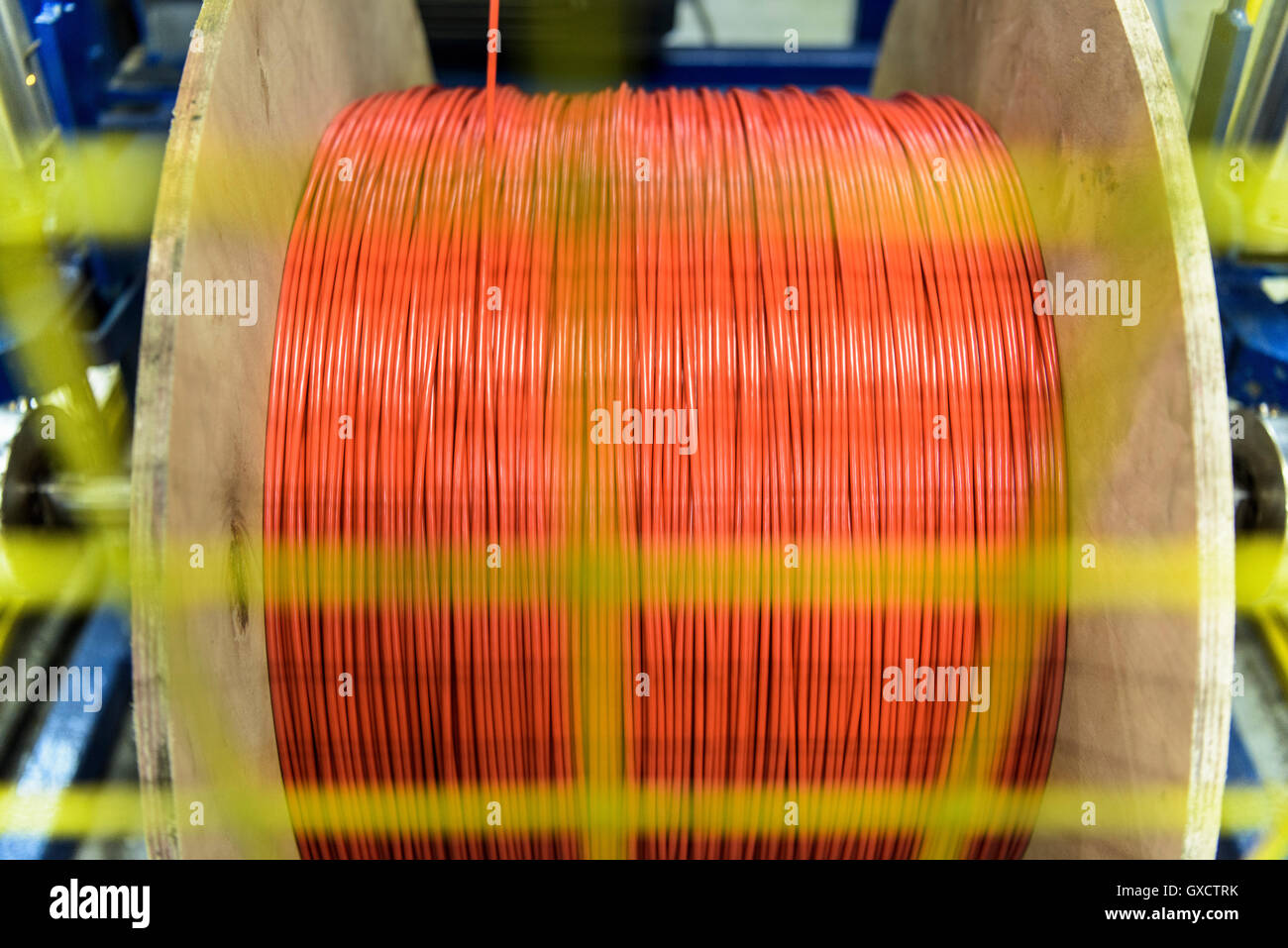 Red cable spinning on spool in cable factory - Stock Image