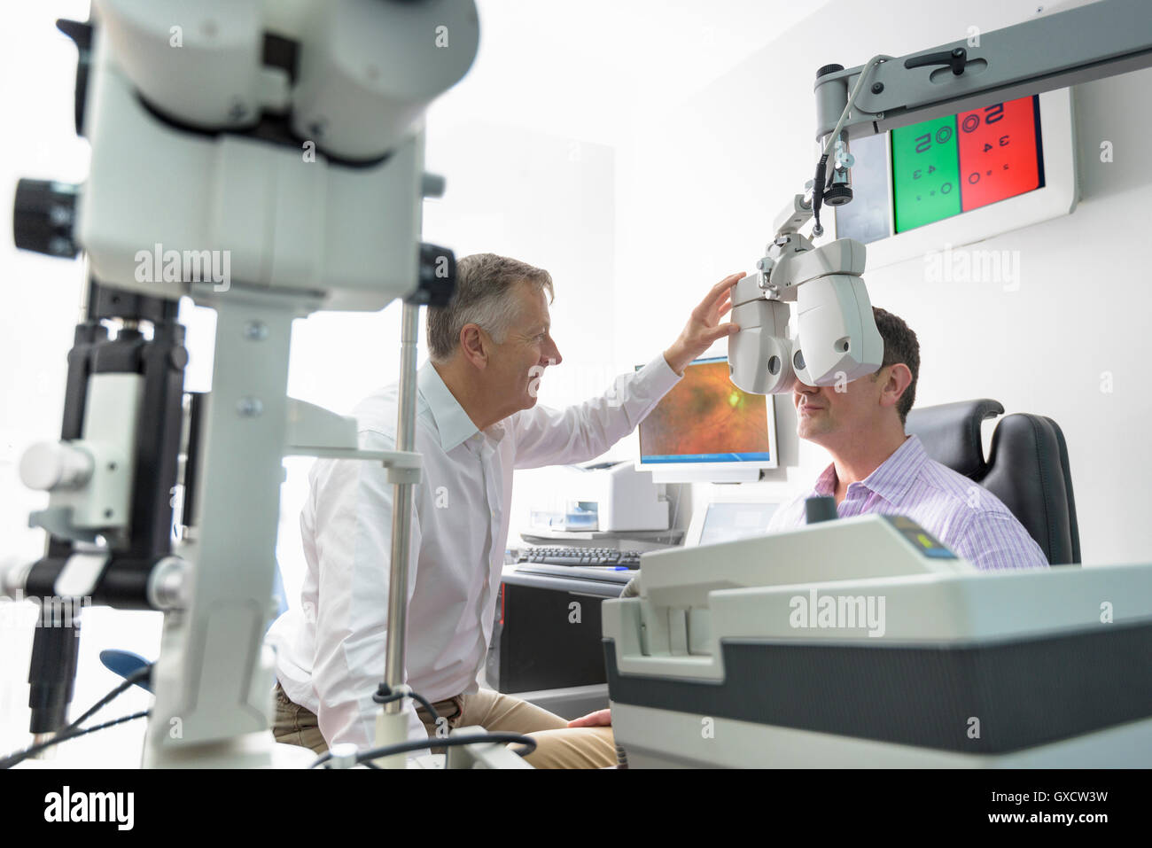 Optician measuring patient's eyes at small business opticians - Stock Image