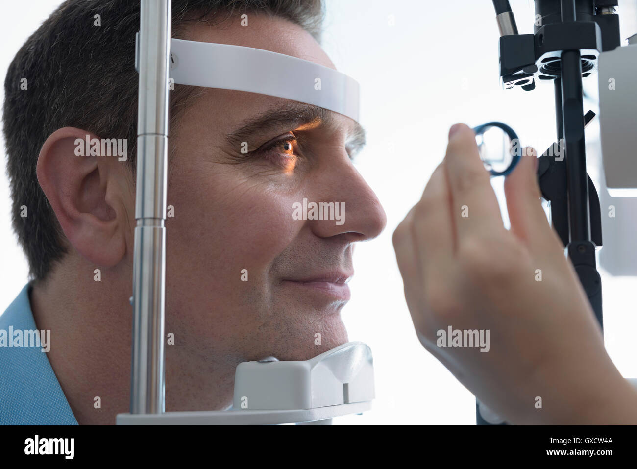 Optician looking into patient's eyes at small business opticians - Stock Image