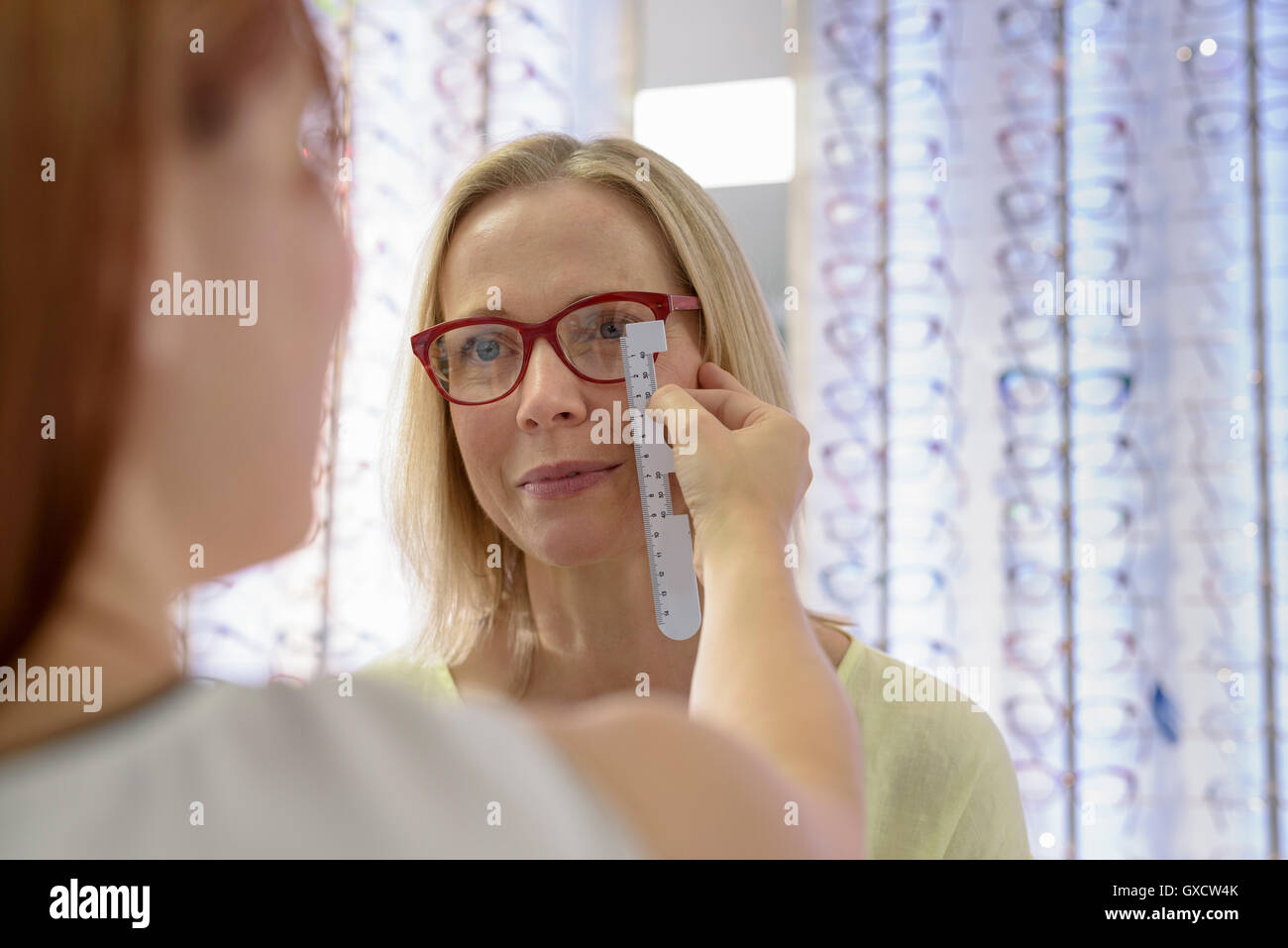 Optician measuring frames for fitting at small business opticians - Stock Image