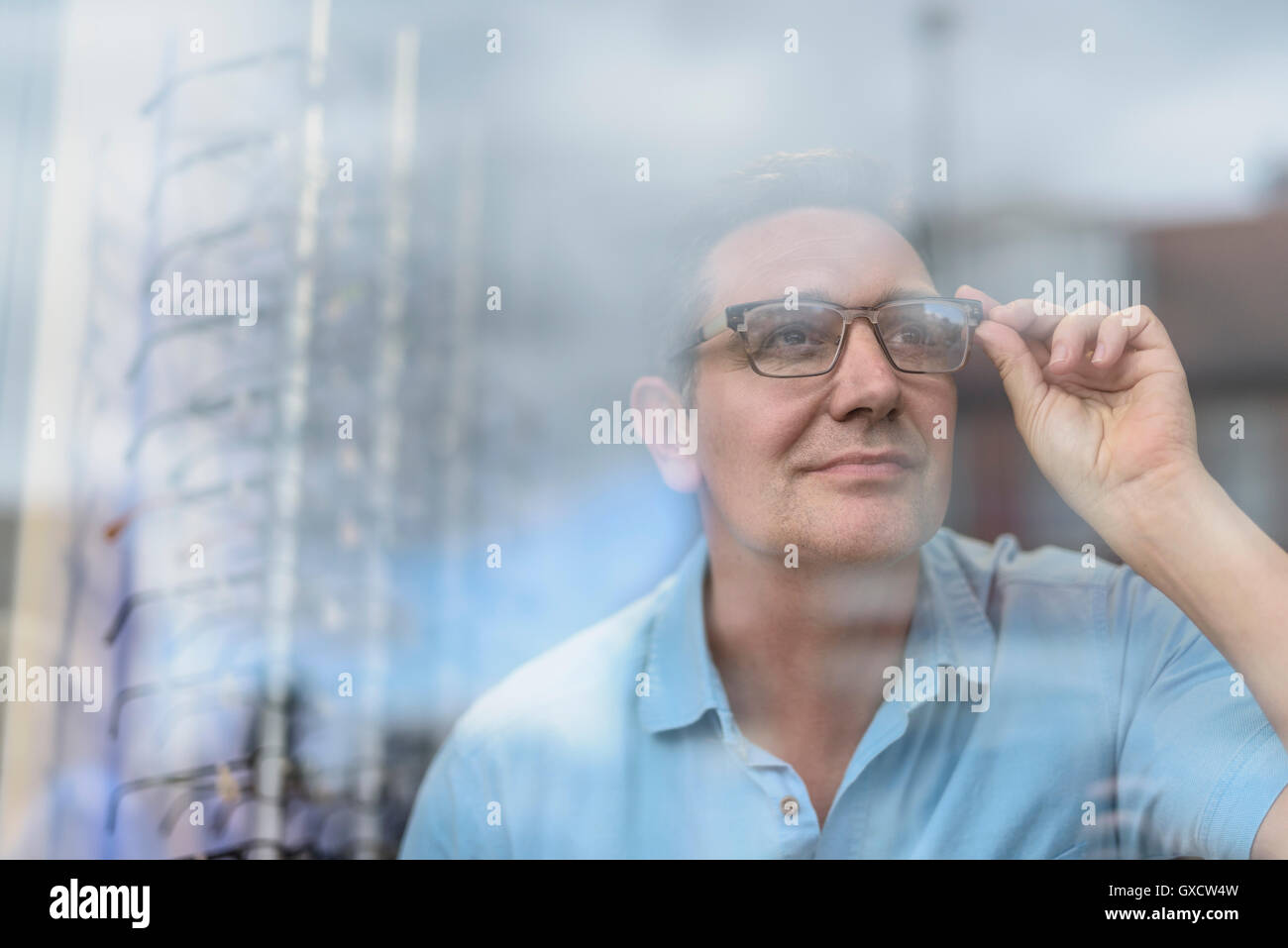 Patient looking through spectacles for first time into street from small business opticians - Stock Image