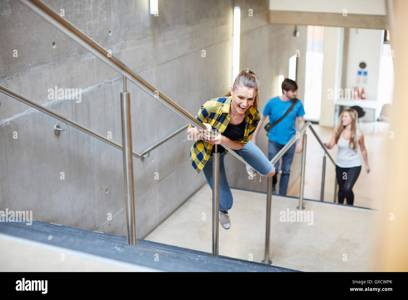 Young female student sliding down stairway handrail at higher education college - Stock Image