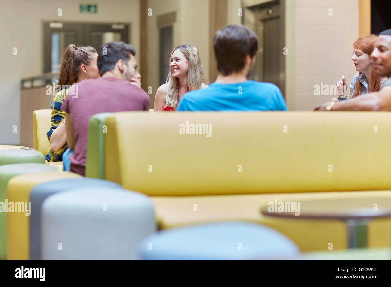 Group of students chatting in canteen at higher education college - Stock Image