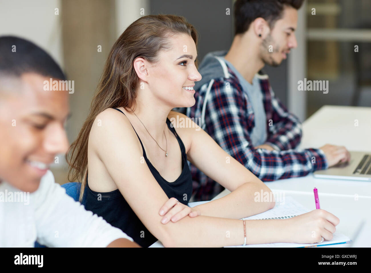 Students taking notes in higher education college classroom - Stock Image