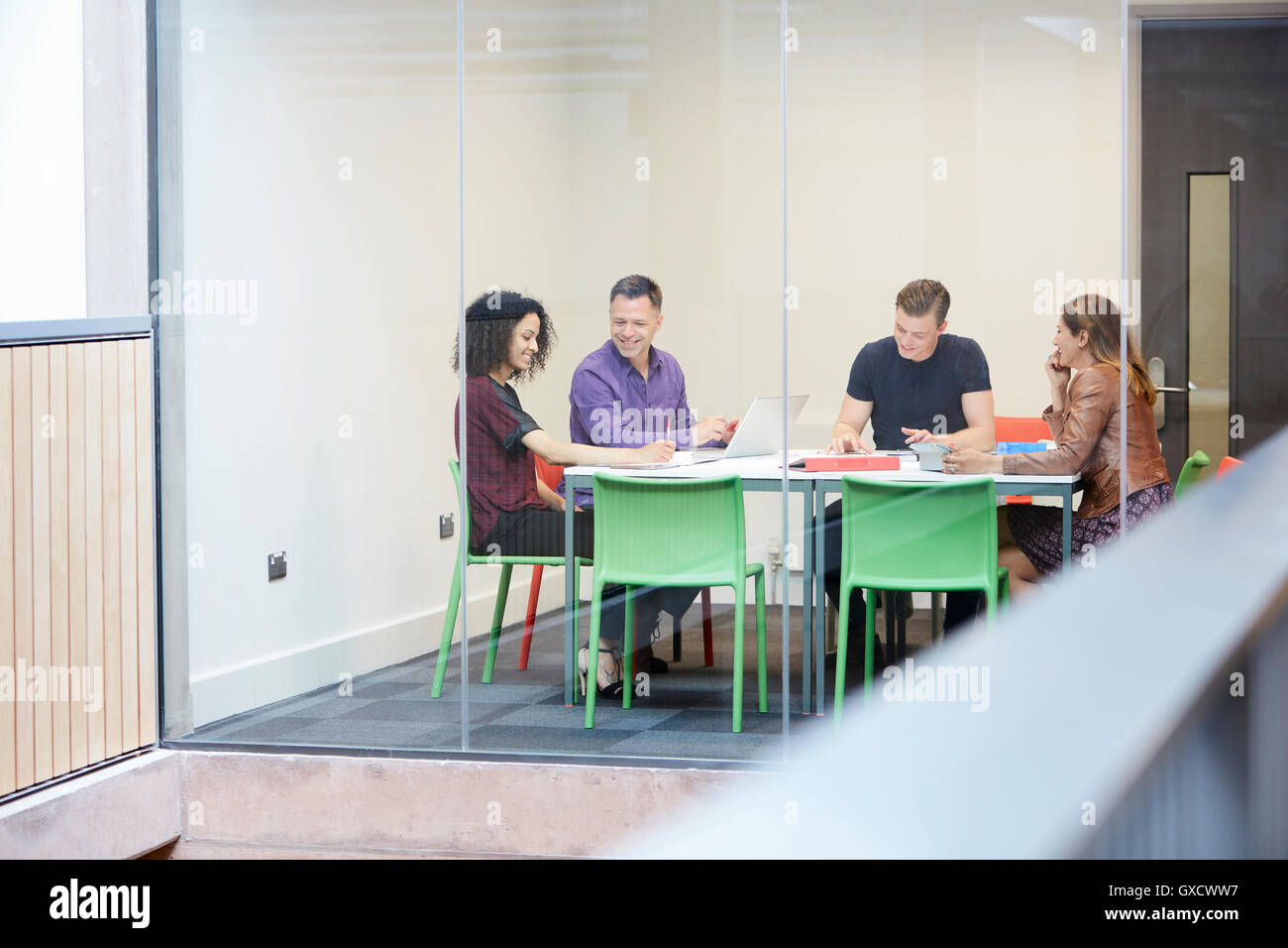 Design team meeting at design studio boardroom table - Stock Image