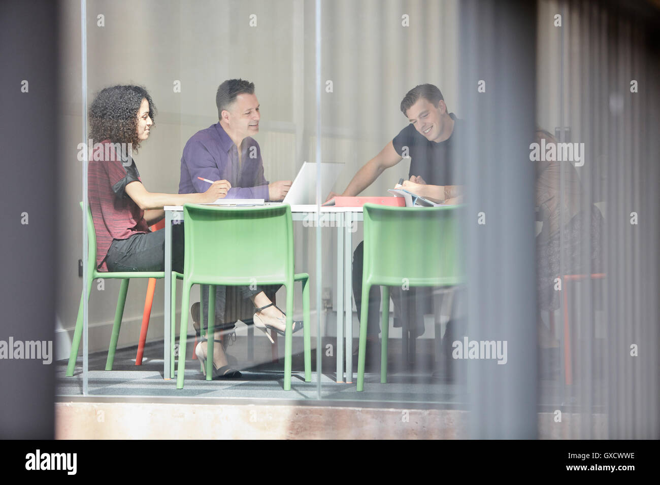 Design team brainstorming at design studio boardroom table - Stock Image