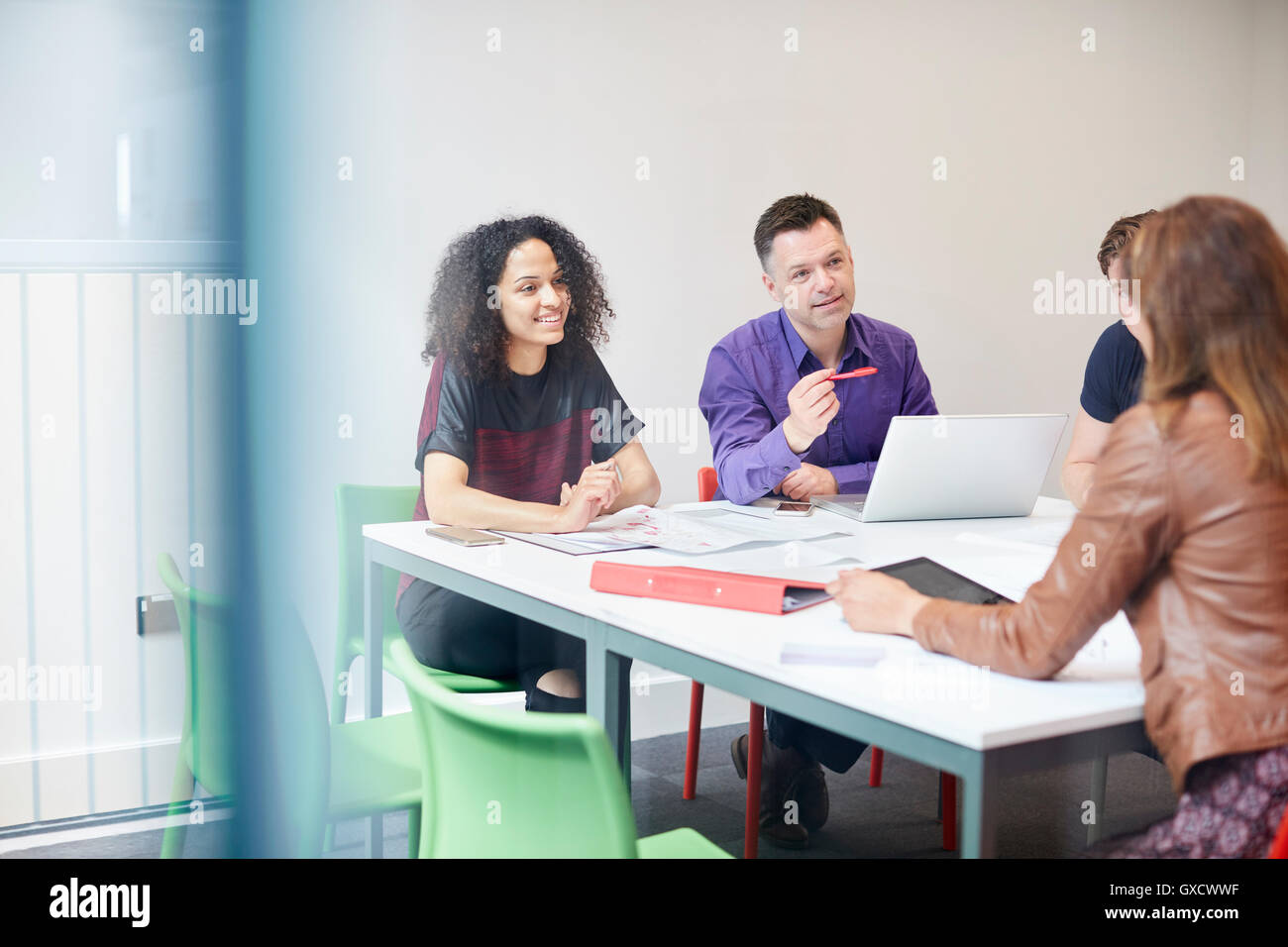 Designers having meeting at design studio boardroom table - Stock Image