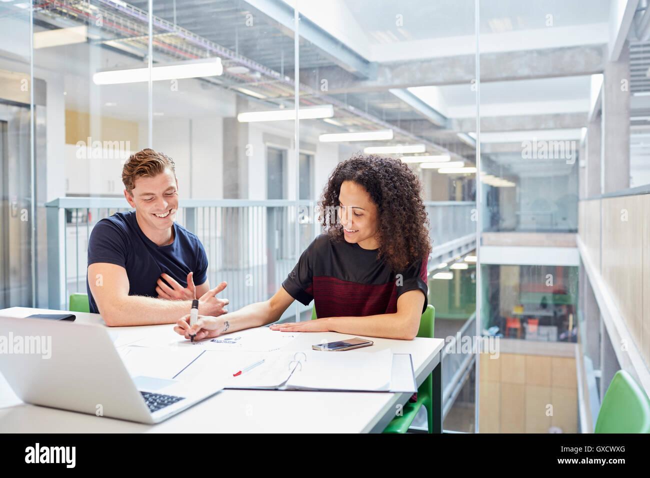 Male and female designers brainstorming in design studio - Stock Image