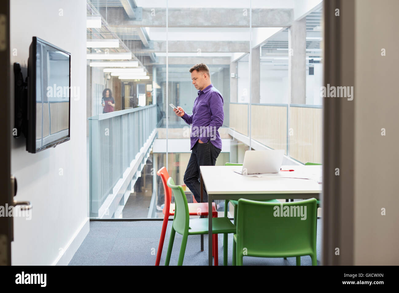 Male designer reading smartphone update in design studio - Stock Image