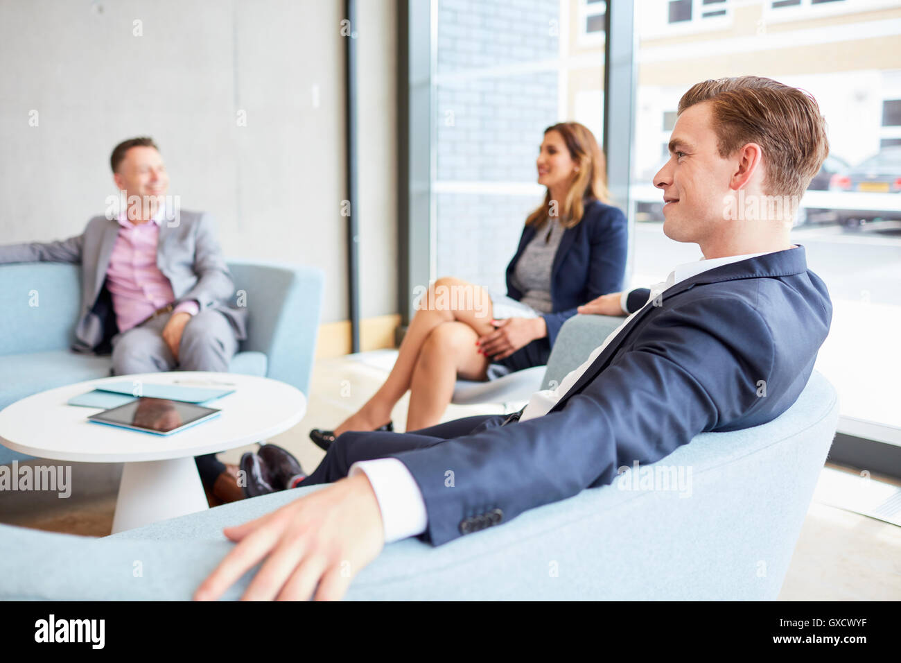 Businessmen and businesswoman meeting on office sofas - Stock Image