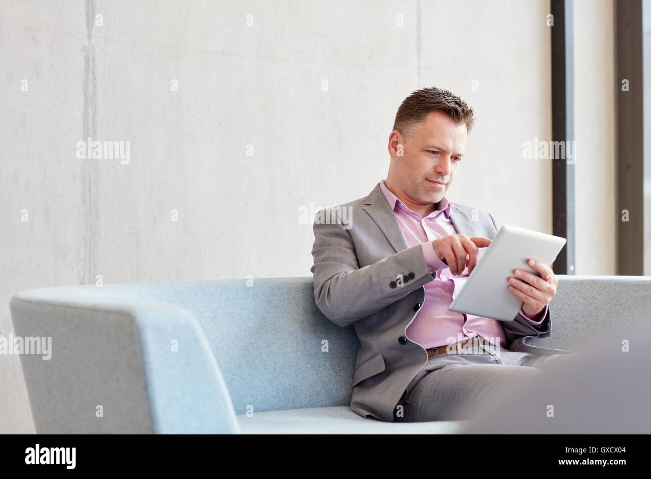Businessman using digital tablet touchscreen in office - Stock Image