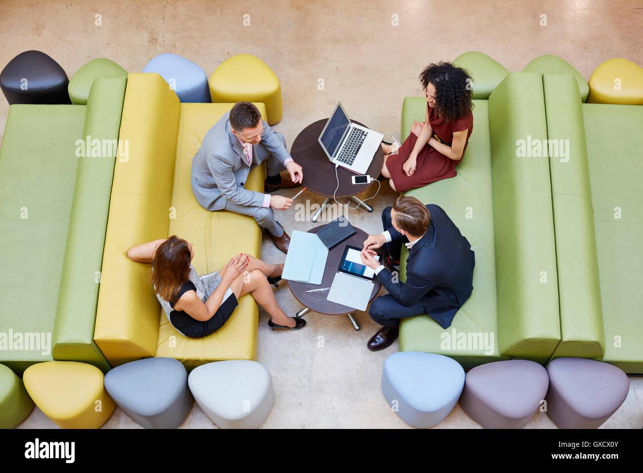 Overhead view of businessmen and businesswomen meeting on design studio sofas - Stock Image