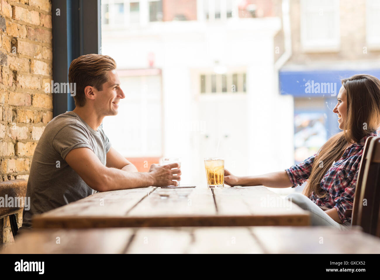 Young couple chatting in bar - Stock Image