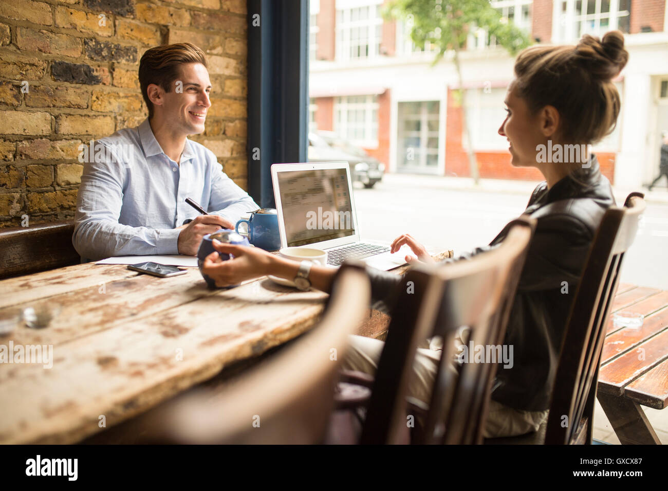 Businessman and woman working in cafe, London, UK - Stock Image